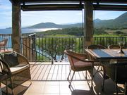 Blick vom Wohn-/Essbereich auf überdachte Terrasse und Meer