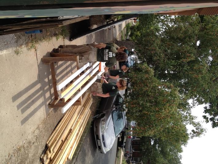 Americore Volunteers painting lumber