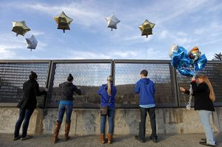 Five Danbury, CT residents tie balloons to an overpass up the road from the Sandy Hook Elementary School (AP Photo/David Goldman)