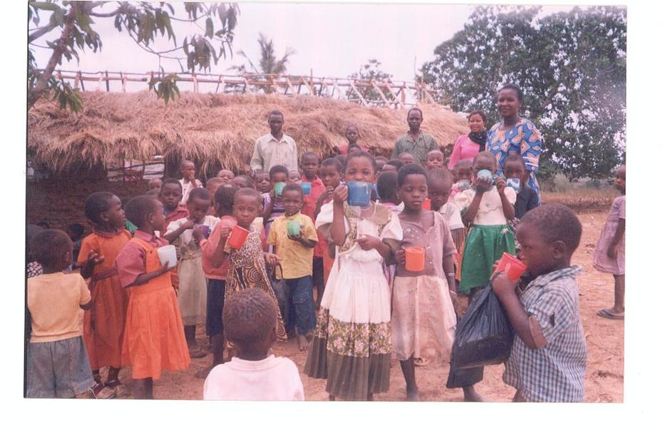Orphan children from Wayani Orphaned day care centre, enjoy their feeding programme out side their grass thatched classroom.