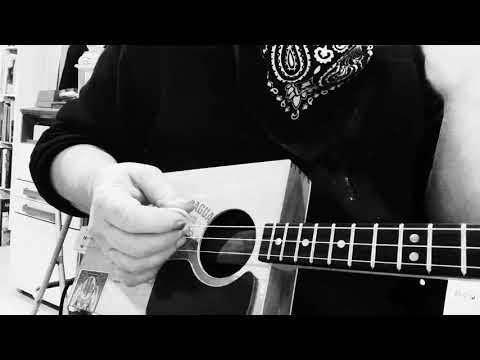 Learning the basics of a simple blues shuffle on Cigar Box Guitar, with Chickenbone John